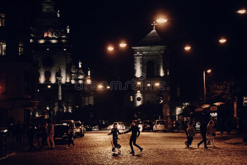 Amantes que corren a través del camino vacío en la calle de la ciudad de la tarde ST imágenes de archivo libres de regalías