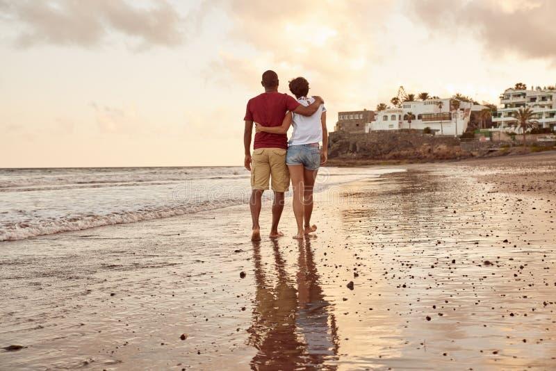 Amantes que dan un paseo a casa en la puesta del sol fotografía de archivo