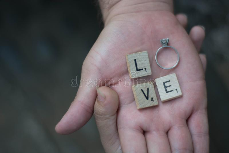 Amantes que guardam as mãos com letras e um anel que soletra a palavra fotos de stock royalty free