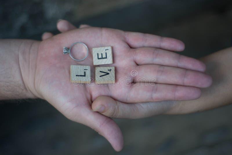 Amantes que guardam as mãos com letras e um anel que soletra a palavra fotos de stock