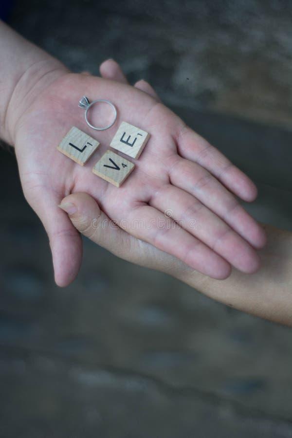 Amantes que guardam as mãos com letras e um anel que soletra a palavra imagens de stock