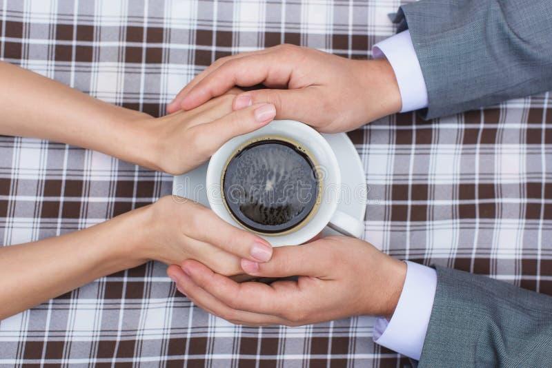 Amantes que mantêm unida uma xícara de café imagens de stock royalty free