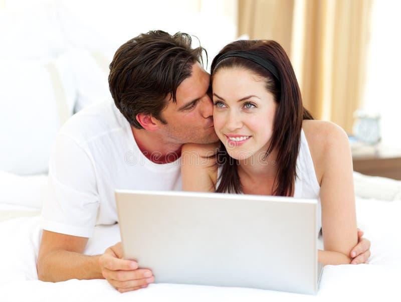 Amantes que usan la computadora portátil que miente en la cama foto de archivo