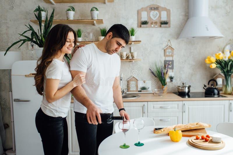 Amantes sonrientes que beben el vino blanco en la cocina imagen de archivo libre de regalías