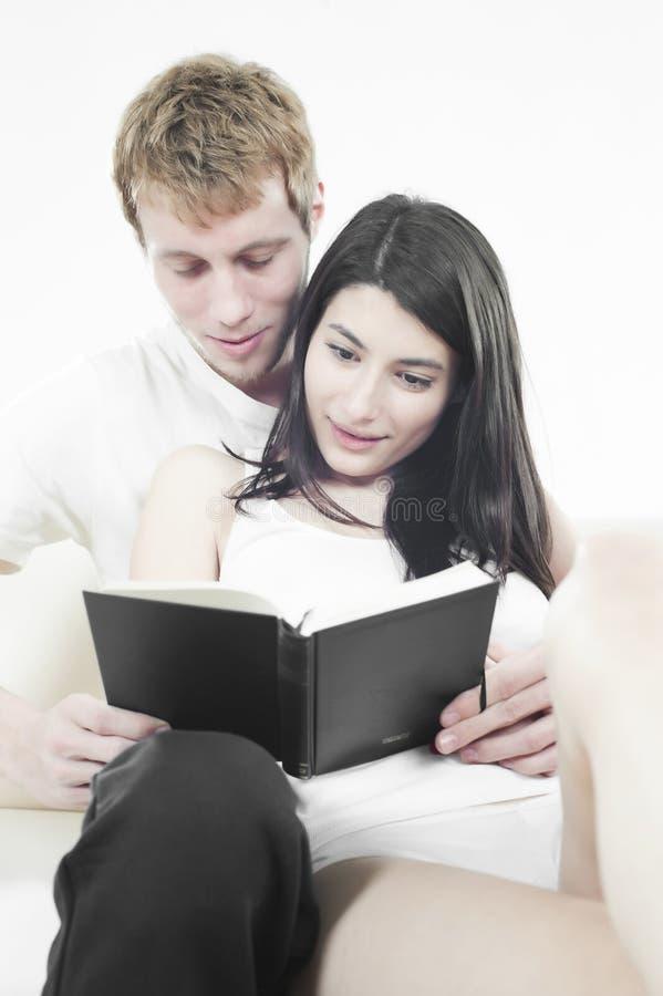 Amanti che leggono un libro sul sofà fotografie stock