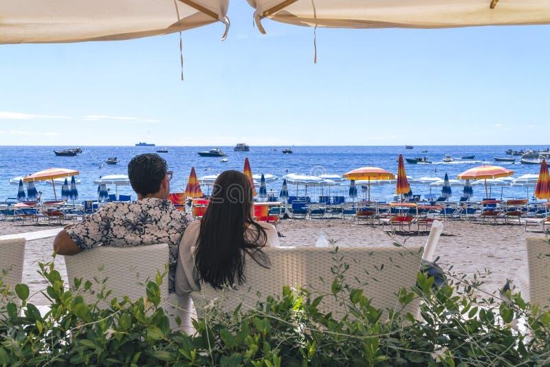 Amanti che si siedono, esaminando cielo e mare, mountion, sotto l'ombrello di sole Vacanza, turismo, hooneymoon Ragazza con i cap fotografia stock libera da diritti