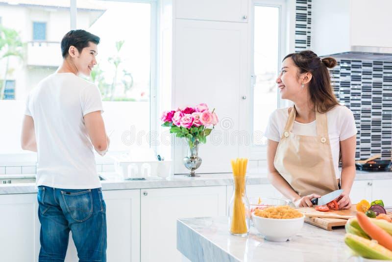 Amanti o coppie asiatici che cucinano insieme così divertente nello spirito della cucina fotografia stock libera da diritti
