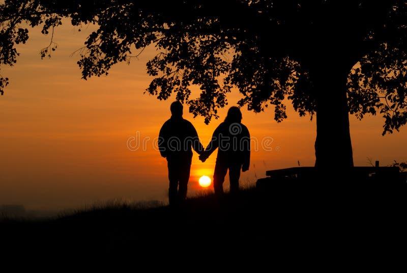 Amants dans le coucher du soleil photos stock