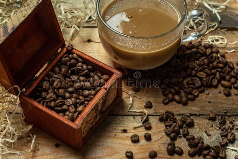 Amants de café - une tasse de café en verre avec du lait pendant le matin, à côté des grains de café rôtis, sur une table en bois image stock