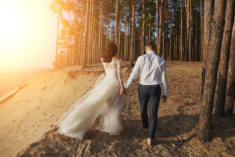Amants de Photoshoot dans une robe de mariage sur la plage près de la mer image libre de droits