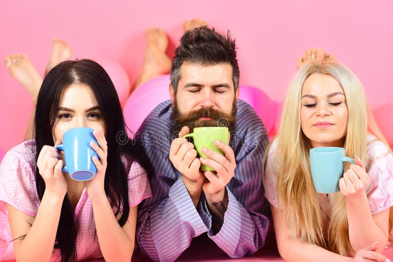 Amants en café de boissons d'amour dans le lit Le plan à trois détendent dans le matin avec du café Concept d'amants Homme et fem images libres de droits