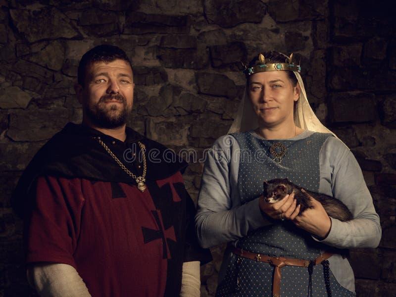 Amants médiévaux Ajouter féeriques à une belette dans des costumes photos libres de droits