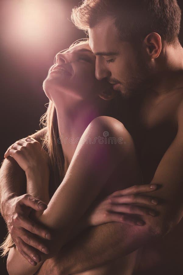amants sensuels étreignant, sur le brun photos stock