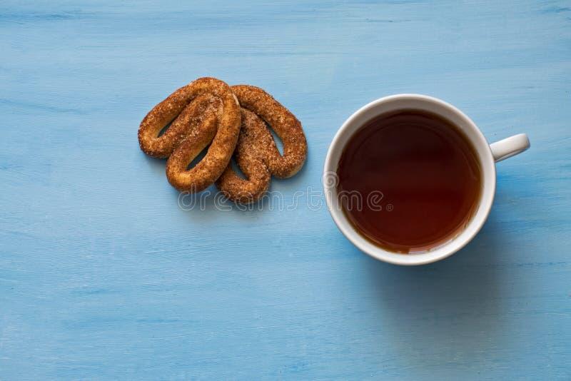 Amapola con los pretzeles en un tablero azul con una taza de té Una taza de té y de pretzeles con canela foto de archivo