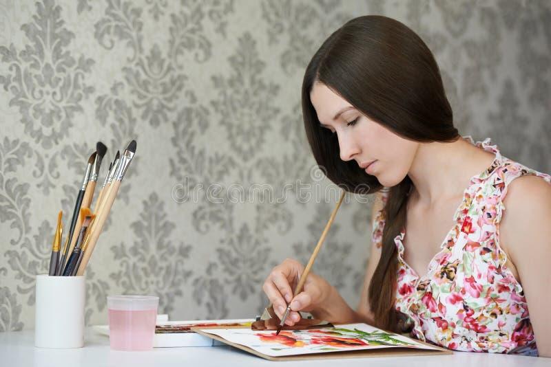 Amapolas de la acuarela del dibujo del pintor de la mujer joven en su estudio casero imágenes de archivo libres de regalías