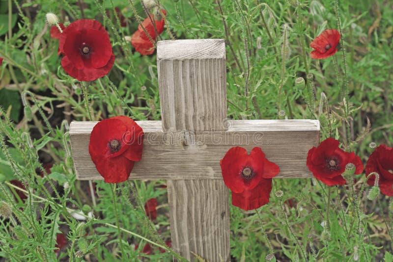 Amapolas del día de la conmemoración y una cruz de madera imágenes de archivo libres de regalías
