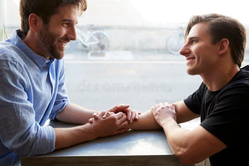 Amar Casal Gay Masculino Sentado À Mesa Na Café Loja Segurando Mãos imagem de stock