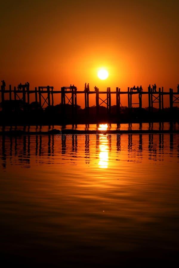 AMARAPURA,缅甸- 11月:未认出的人民在U Bein桥梁走在11月的日落,在Amarapura,缅甸 U 免版税图库摄影