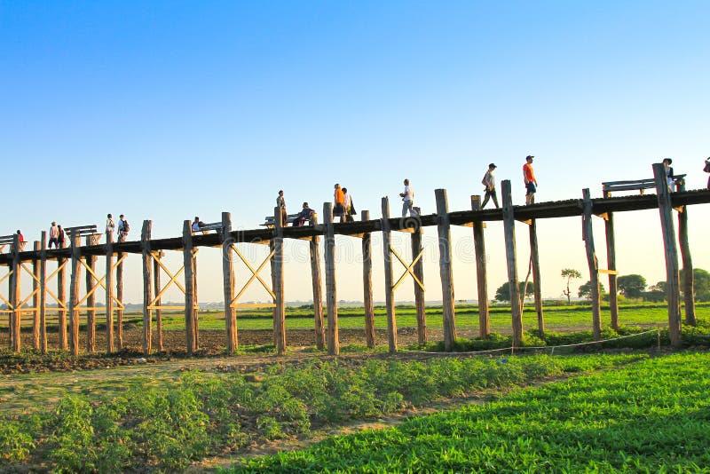 AMARAPURA, MYANMAR - NOVIEMBRE: La gente no identificada camina en el puente de U Bein en la puesta del sol en noviembre, en Amar foto de archivo