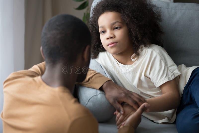 Amare il padre nero parla sostenendo la figlia sconvolta fotografie stock