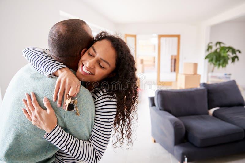 Amare Una Coppia Abbracciando Le Chiavi Per Una Nuova Casa Nel Giorno Del Movimento immagine stock