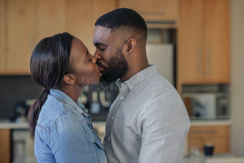 Amare una giovane coppia afro-americana baciarsi a casa fotografie stock