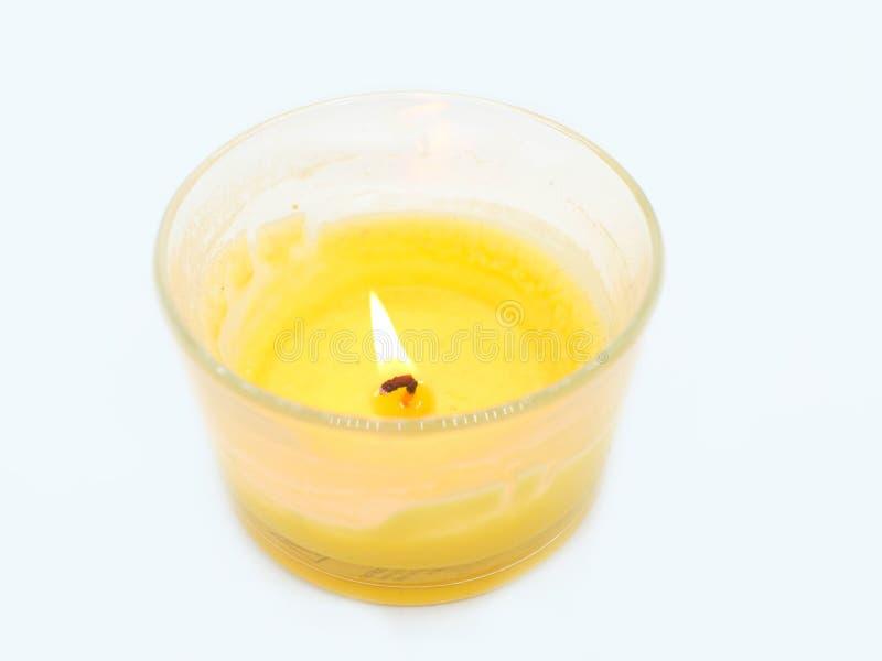Amarele a vela iluminada em um vidro em um fundo branco fotografia de stock royalty free