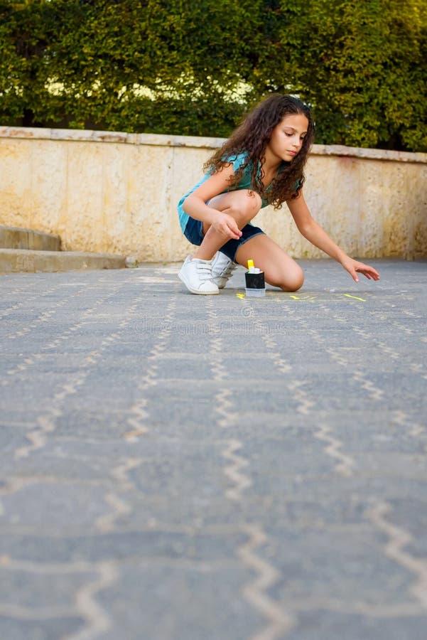 Amarelinhas de tiragem da menina com giz no campo de jogos fotografia de stock