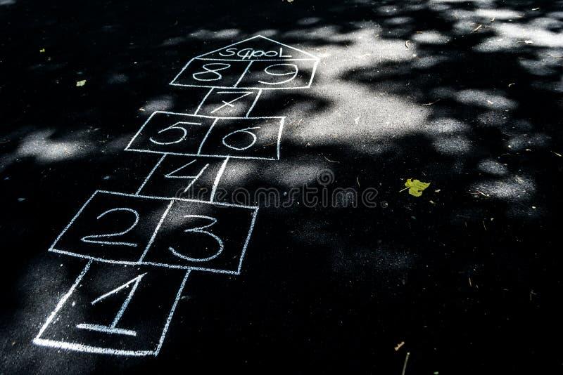 Amarelinhas tiradas com giz no asfalto preto imagens de stock
