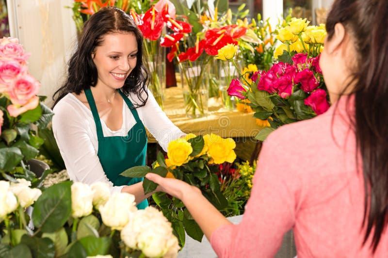 Amarelo de compra do cliente alegre do florista do florista foto de stock