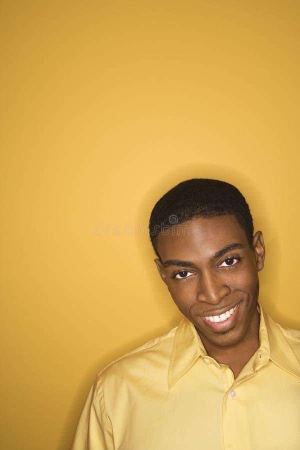 Amarelo desgastando do homem do African-American no fundo amarelo. fotografia de stock royalty free
