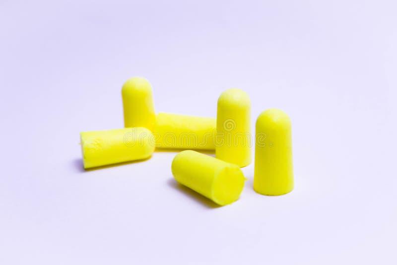 Amarelo do tampão de ouvido das tomadas das orelhas dos múltiplos isolado no sono branco do trabalho imagem de stock