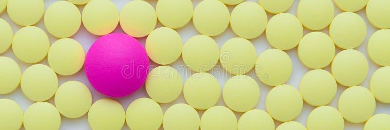 Amarelo pequeno e comprimidos um cor-de-rosa em um close-up branco do fundo fotos de stock royalty free