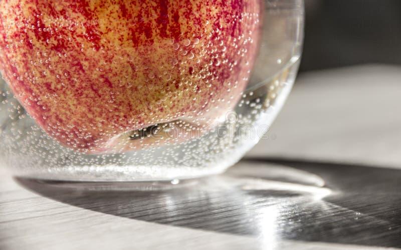 Amarillo anaranjado rojo de Apple en un florero con agua en las burbujas de aire horizontales en la macro del primer de la llamar imagen de archivo libre de regalías