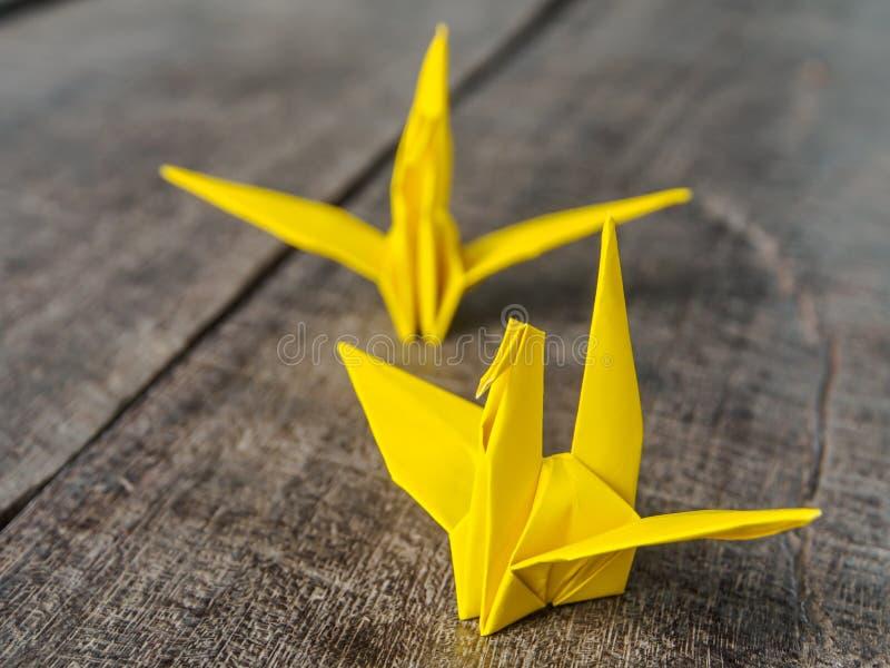 Amarillo de papel del pájaro en de madera foto de archivo libre de regalías