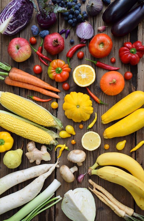 Amarillo, naranja, frutas y verduras rojas, púrpuras en fondo de madera Alimento sano Comida cruda multicolora Copie el espacio foto de archivo