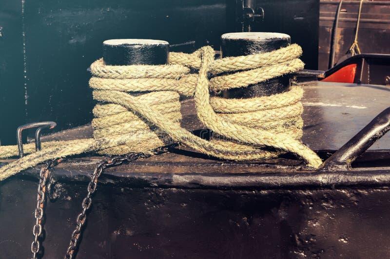 Amarrage des bornes avec la corde approximative sur le vieux bateau noir photographie stock libre de droits