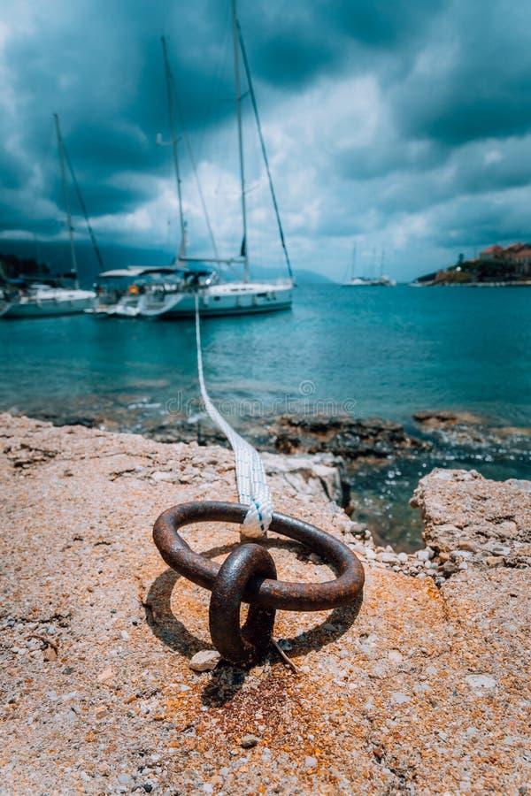 Amarrando a corda e o poste de amarração na água do mar e no iate no fundo Nuvens chuvosas dramáticas acima do mar Mediterrâneo foto de stock