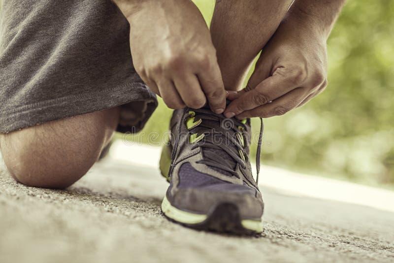Amarrando a sapata dos esportes na estrada imagem de stock