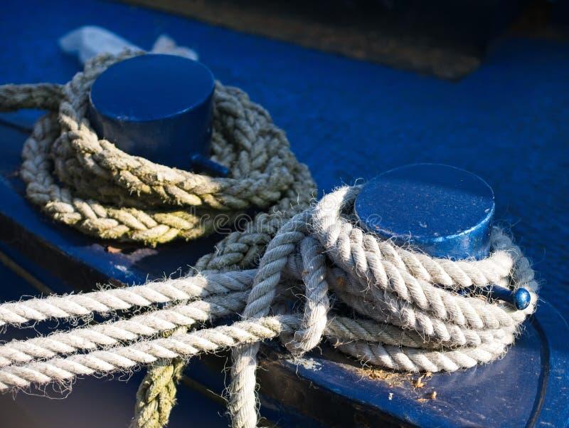 Amarrant des cordes attach?es aux bornes bleues de fer du bateau image libre de droits