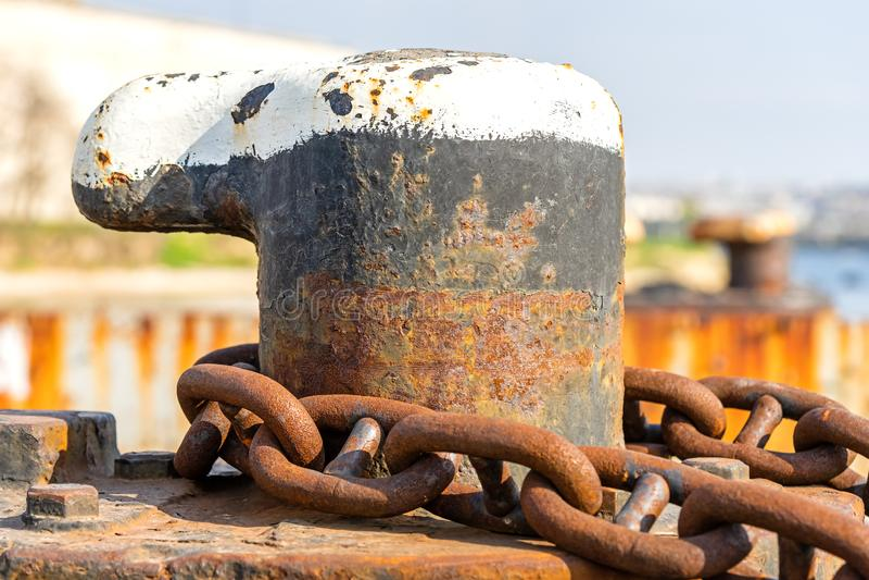 Amarrar el bolardo y la cadena de ancla oxidada imagenes de archivo