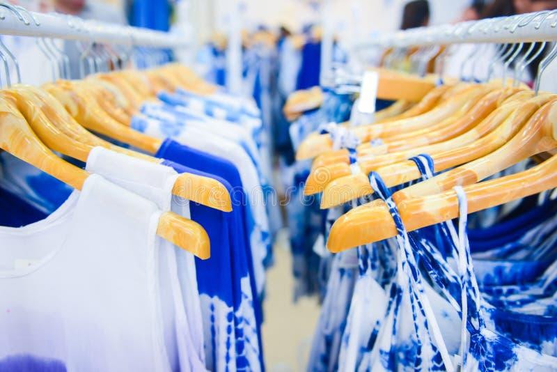 Amarre as camisas e a tela da tintura que penduram em ganchos em uma loja imagem de stock royalty free