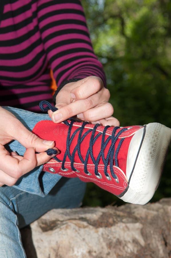 Amarre os laços nas sapatilhas foto de stock