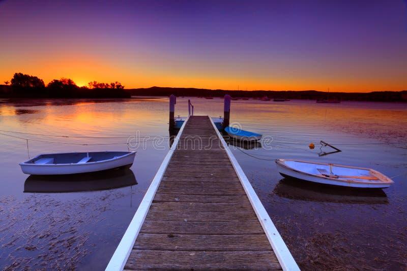 Amarres de la puesta del sol y embarcadero del barco en una pequeña ensenada Australia imagenes de archivo