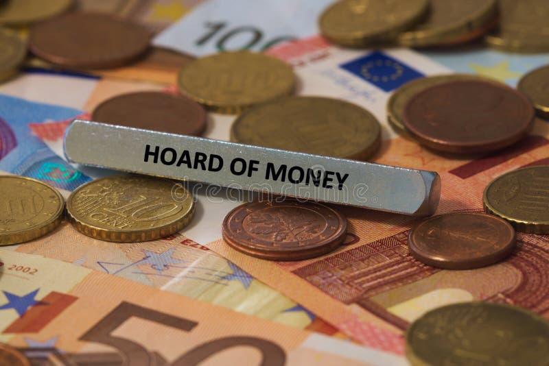 amas d'argent - le mot a été imprimé sur une barre en métal la barre en métal a été placée sur plusieurs billets de banque photographie stock libre de droits