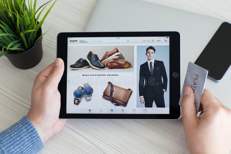 Amason för service för shopping för internet för hållande iPad för man pro-på skärmen arkivfoton