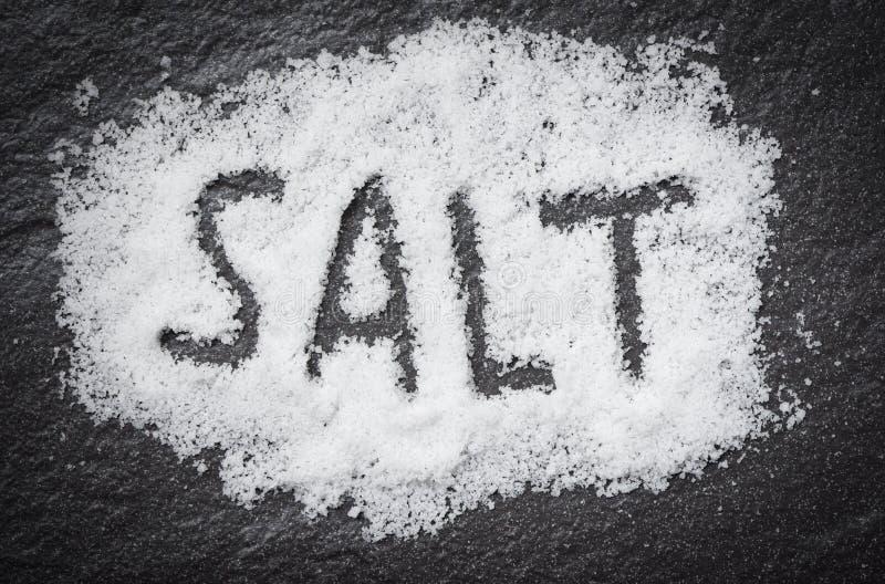 Amassez le sel blanc sur le fond foncé avec du SEL des textes images stock