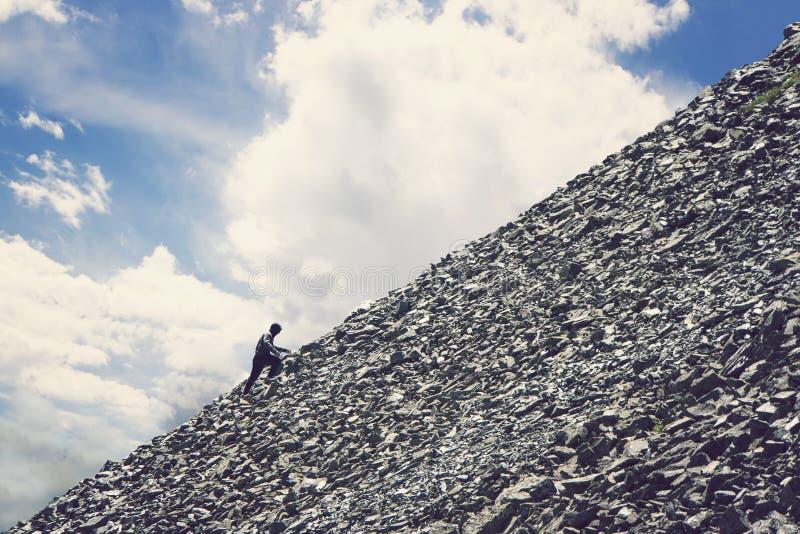 Amatörmässig bergsbestigning mot den blåa himlen med moln Man att klättra upp kullen för att nå maximumet av berget Ståndaktighet arkivfoton