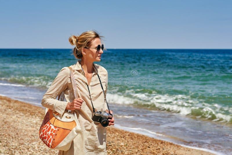 Amatörmässig fotograf för ung kvinna på en gå vid havet med en gammal kamera royaltyfri foto