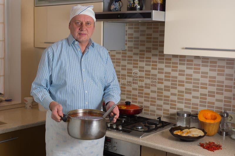 Amatörmässig manlig kock i ett kök arkivfoto